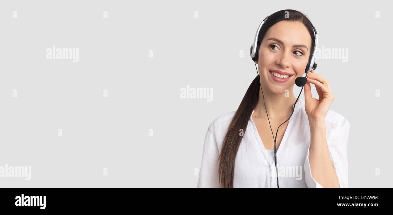 Consultant of call center in headphones on gray background. Helpline operator with headset Stock Photo