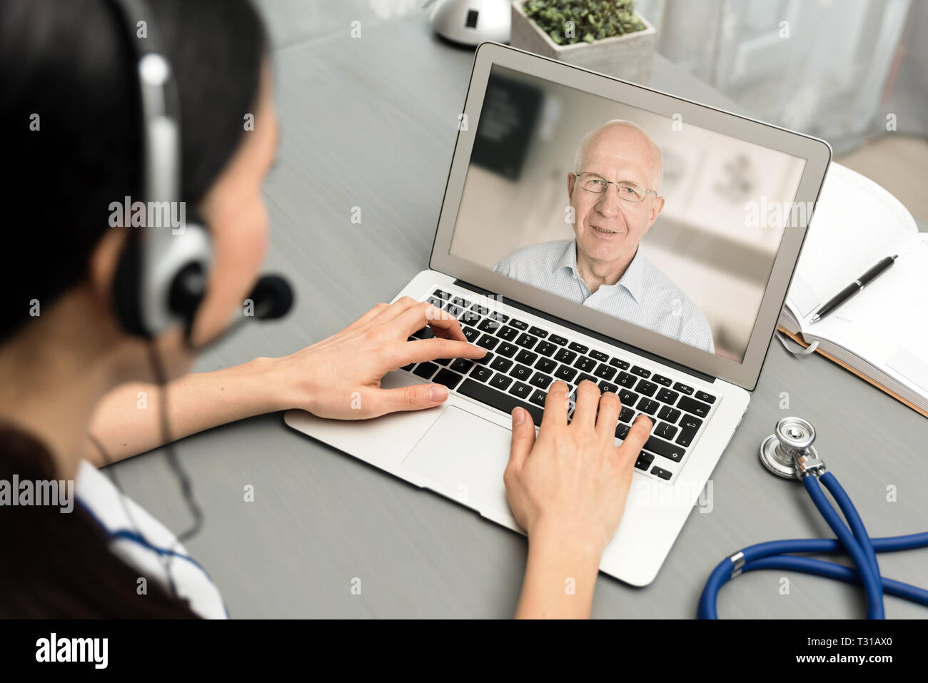 Doctor talking with a senior patient. Telemedicine concept - Stock Image