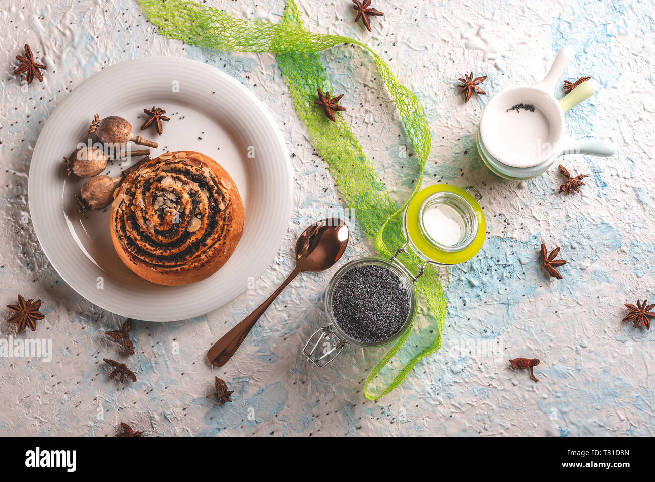 Horizontal photo with top view on sweet rolled bun stuffed by poppy. Bun is on white plate with few poppyheads. Glass gar with poppy seeds and stacked - Stock Image