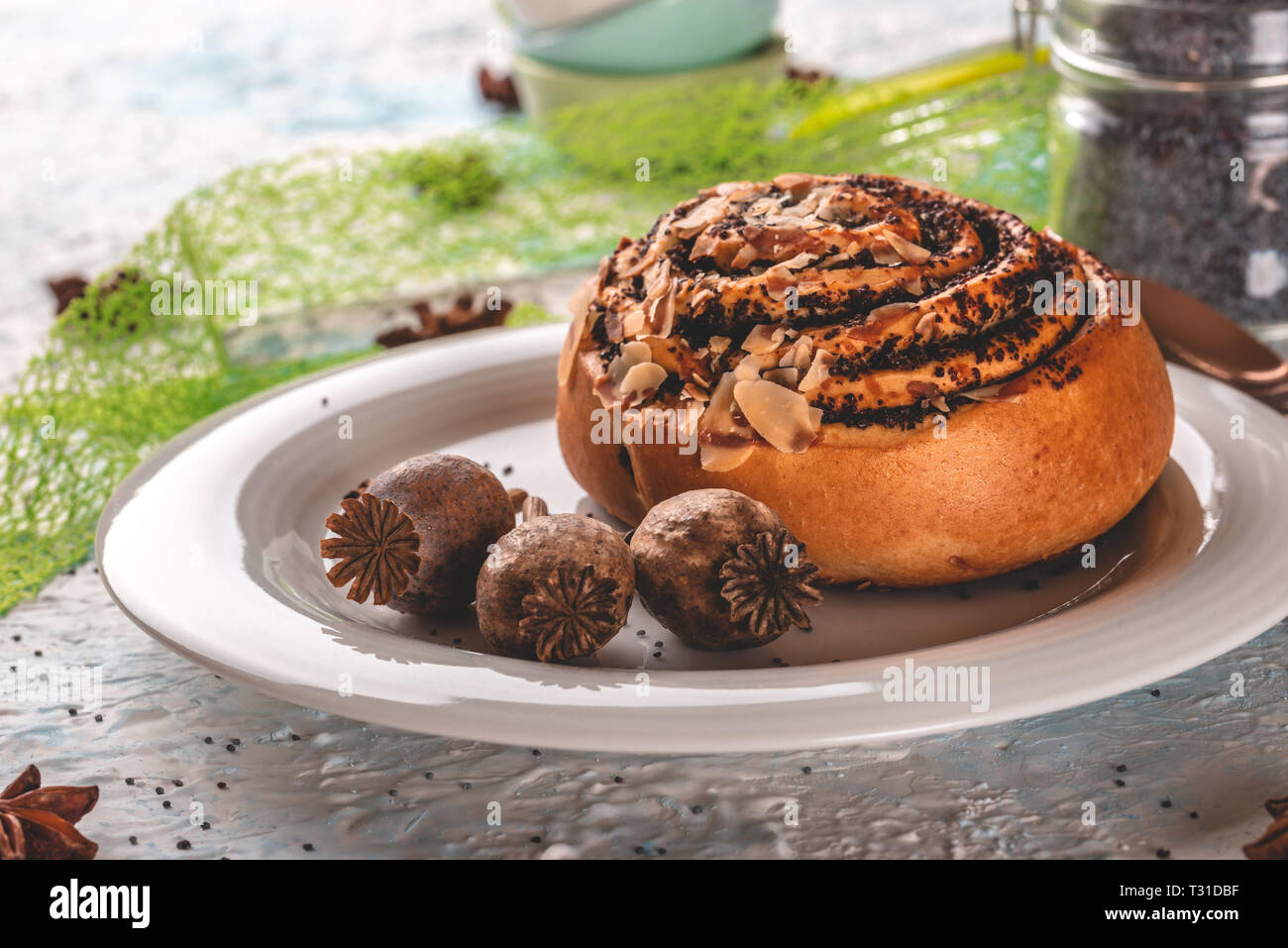 Horizontal photo of sweet rolled bun stuffed by poppy. Bun is on white plate with few poppyheads. Glass gar with poppy seeds and stacked small bowls a - Stock Image