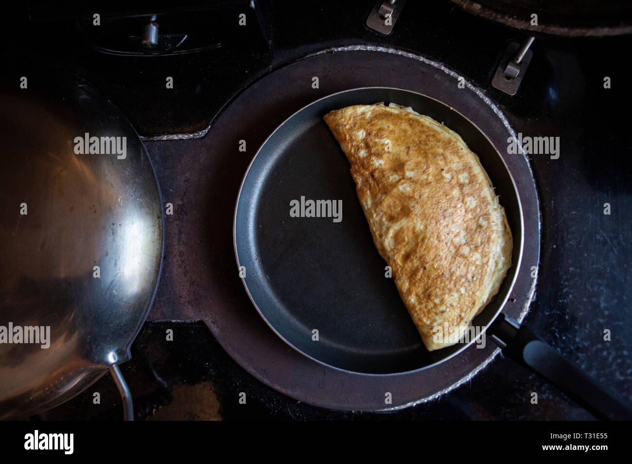 omelette cooking on a stove cooker - Stock Image