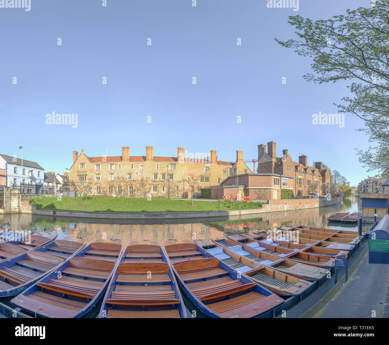 Sunshine on Magdalene college reflected in the river Cam on a sunny spring day at the university of Cambridge, England, with moored punts on the nears - Stock Image