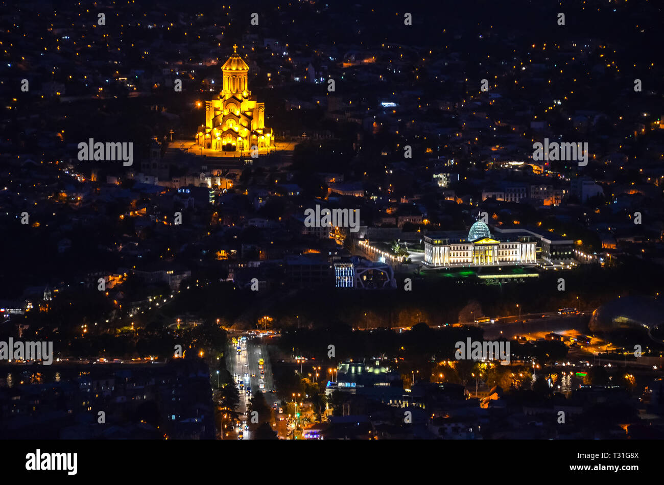 Night view of illuminated Holy Trinity Cathedral and Presidential Palace from Mtatsminda park in Tbilisi - Stock Image