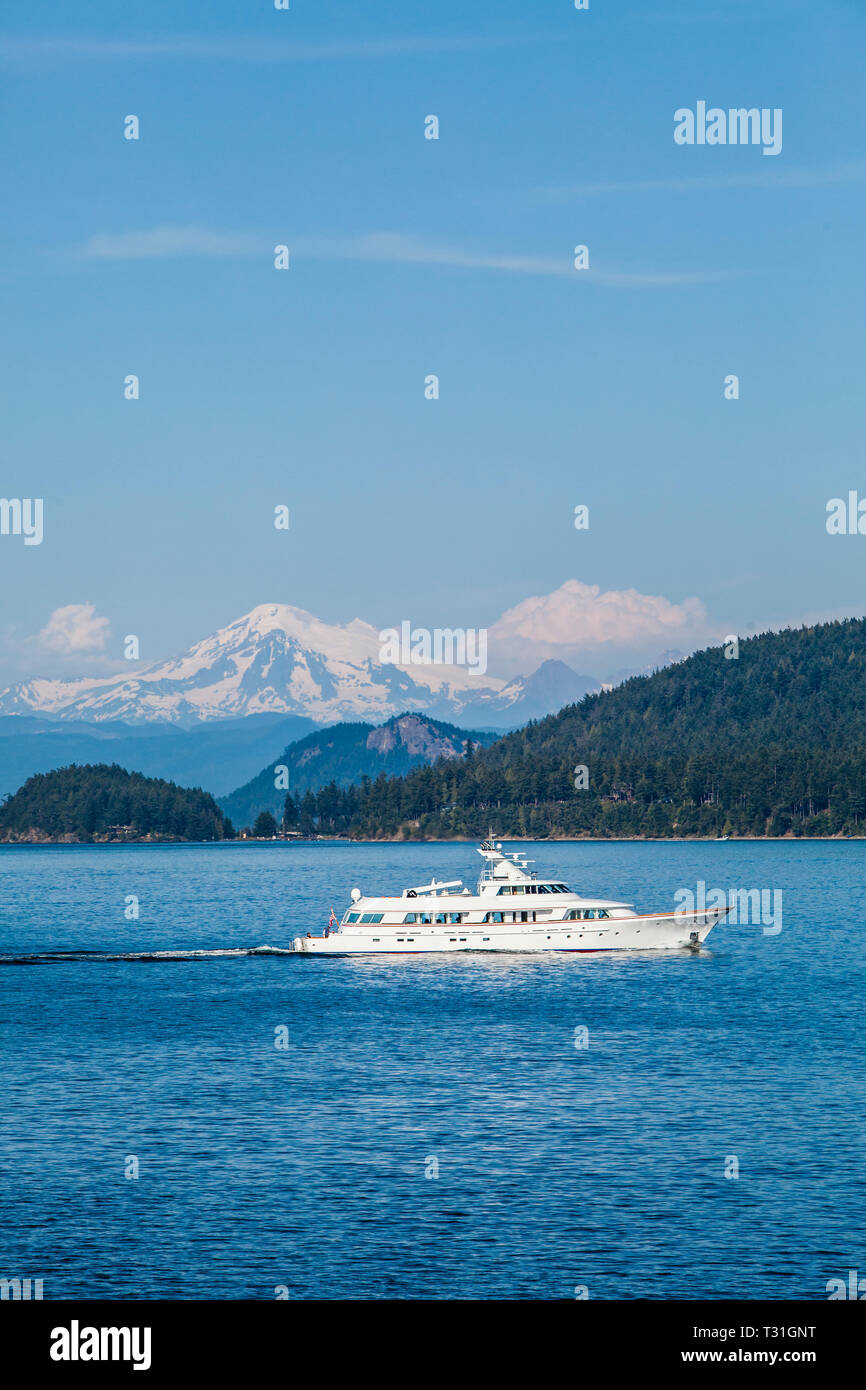 A large pleasure craft or yacht sailing through the San Juan Islands with Mount Baker in the background. Salish Sea, Washington State, USA. - Stock Image