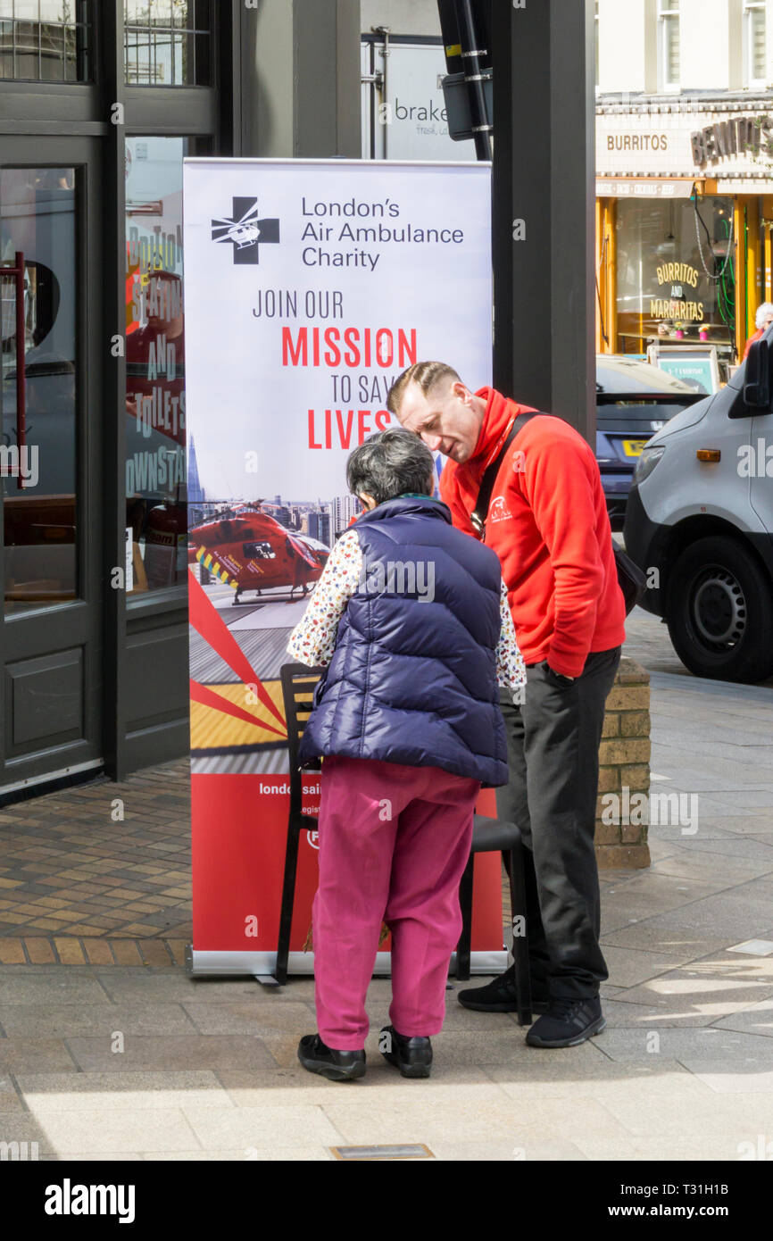 A charity collector with a poster raising support for London's air ambulance. - Stock Image