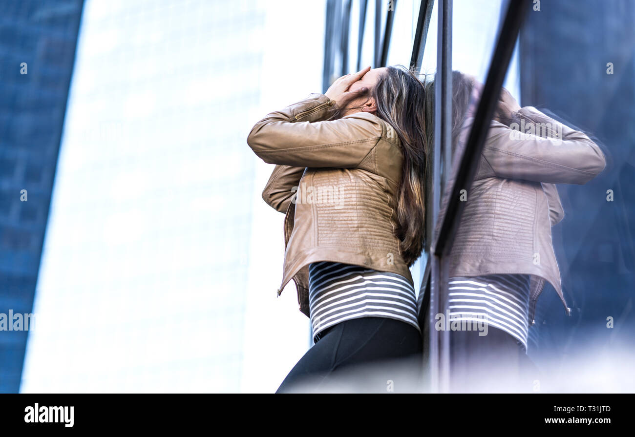 Shame, failure, making mistakes and embarrassment concept. Depressed and hysterical woman crying in city. Embarrassed person covering face with hands. - Stock Image