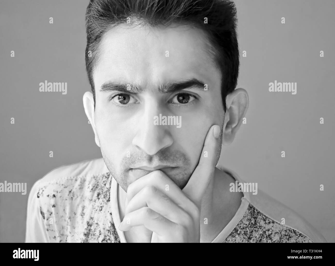 Black and white portrait of young man contemplating - Stock Image