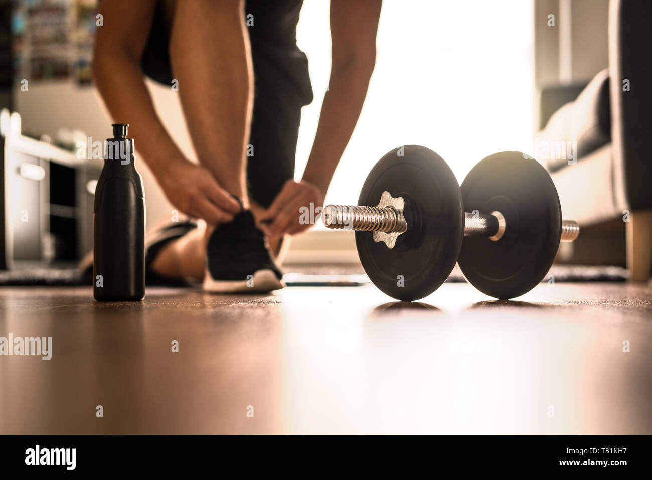 Morning Workout Routine In Home Gym Fitness Motivation And Muscle Training Concept Man In Sneakers Tying Shoelaces In Sunlight Stock Photo Alamy