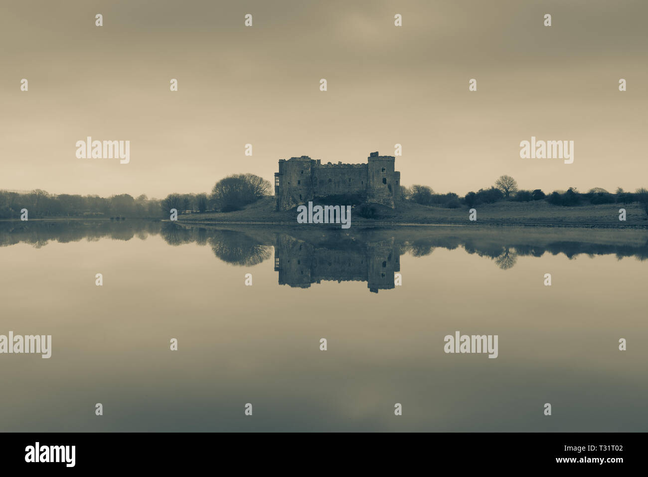 Carew Castle reflecting in the water on a misty morning, Pembrokeshire in sepia tones - Stock Image