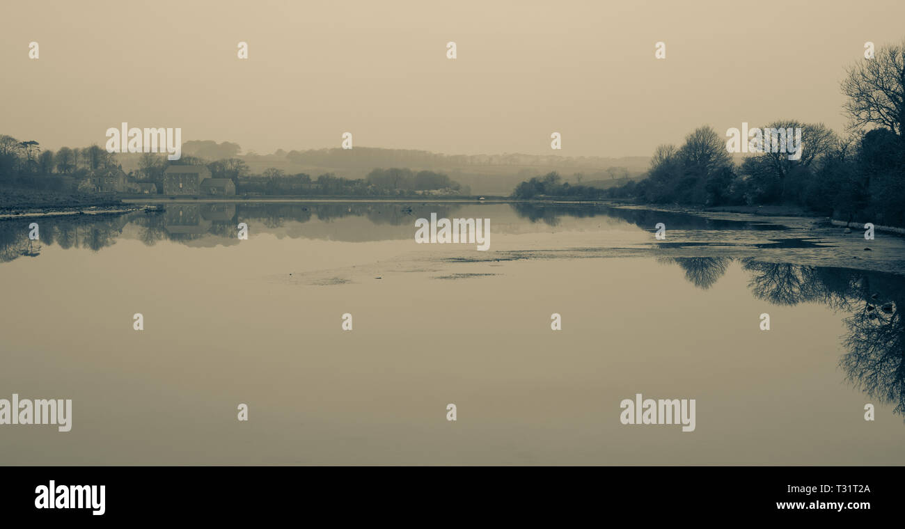 Mill at Carew Castle reflecting in the water on a misty morning, Pembrokeshire, Wales - Stock Image