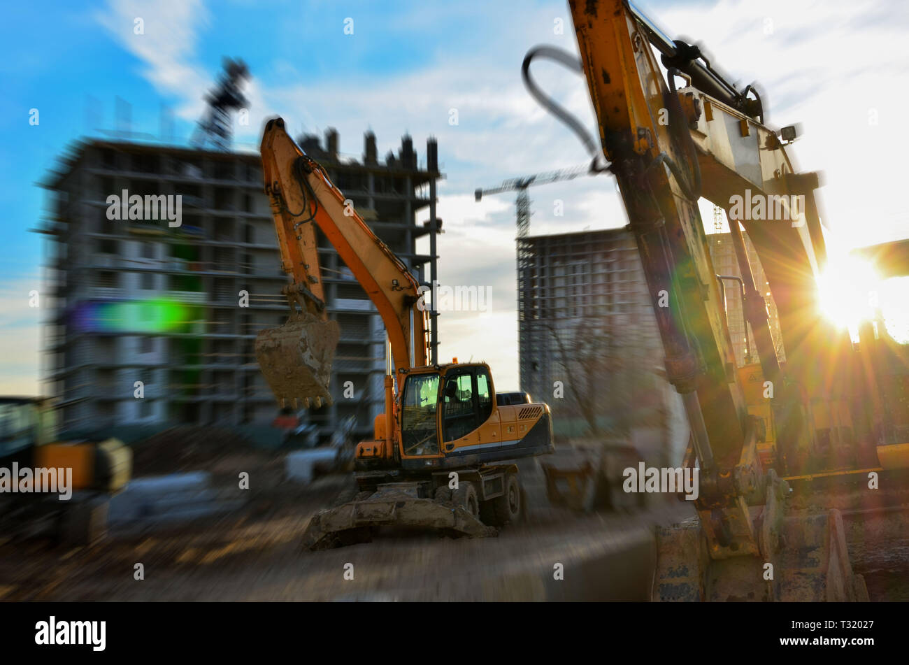 Industrial equipment, earthmoving excavators and construction crane at sunset, sunrise. Blur effect. Under construction site - Image - Stock Image