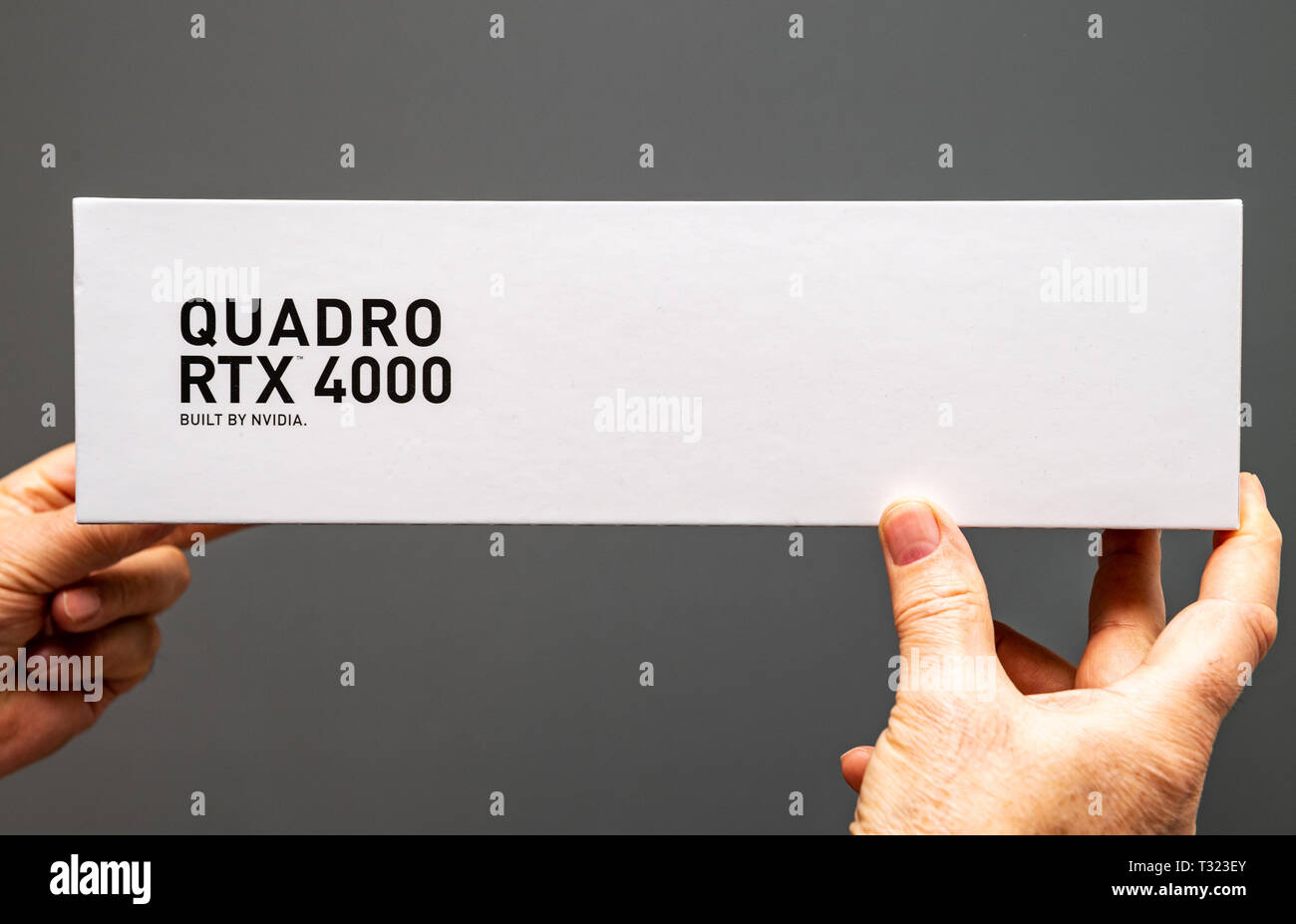 Paris France - Mar 28 2019: Senior man showing cardboard boxes before unboxing of Nvidia Quadro RTX 4000 workstation GPU featuring new streaming multiprocessors tensor cores top view  - Stock Image