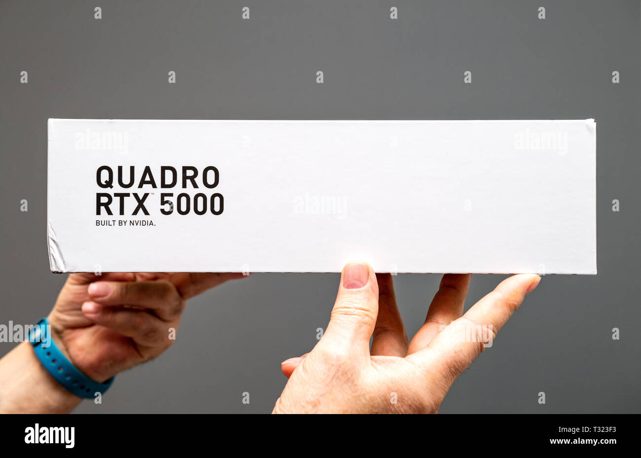 Paris France - Mar 28 2019: Senior man showing cardboard boxes before unboxing of Nvidia Quadro RTX 5000 workstation GPU featuring new streaming multiprocessors tensor cores - gray background - Stock Image