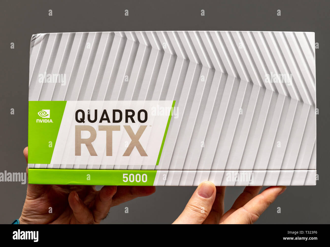 Paris France - Mar 28 2019: Senior man showing cardboard boxes before unboxing of Nvidia Quadro RTX 5000 workstation GPU featuring new tensor cores - gray background - Stock Image