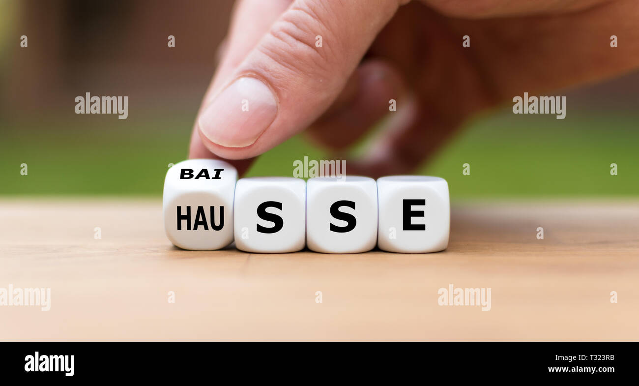 """Symbol for a trend change at the stock market. Hand turns a dice and changes the word """"BAISSE"""" to """"Hausse"""". Stock Photo"""