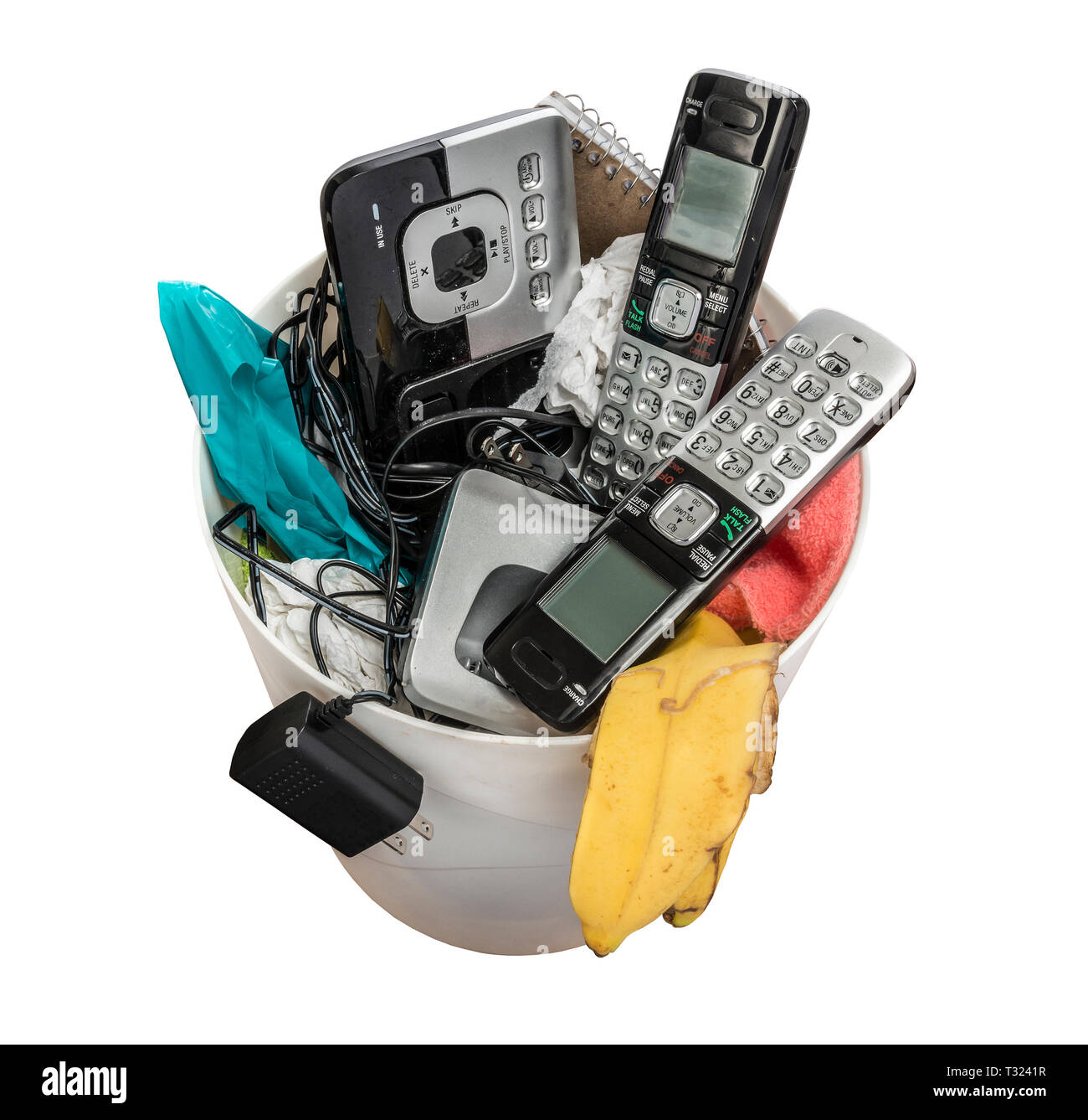 Horizontal shot of land line telephones thrown away in a trashcan.  This shot is looking down on the trashcan. Stock Photo