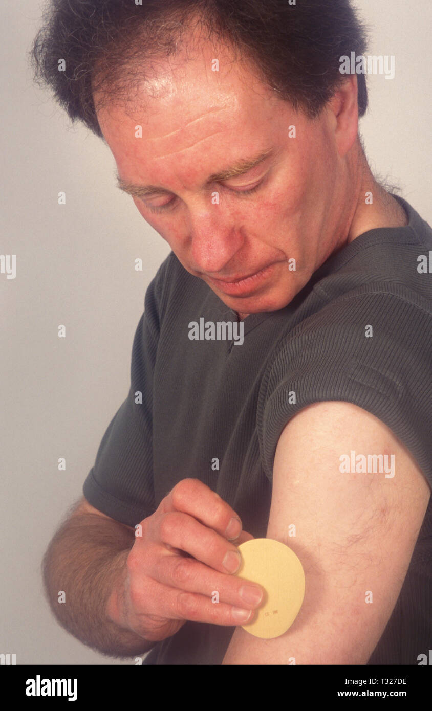 man applying nicotine patch - Stock Image