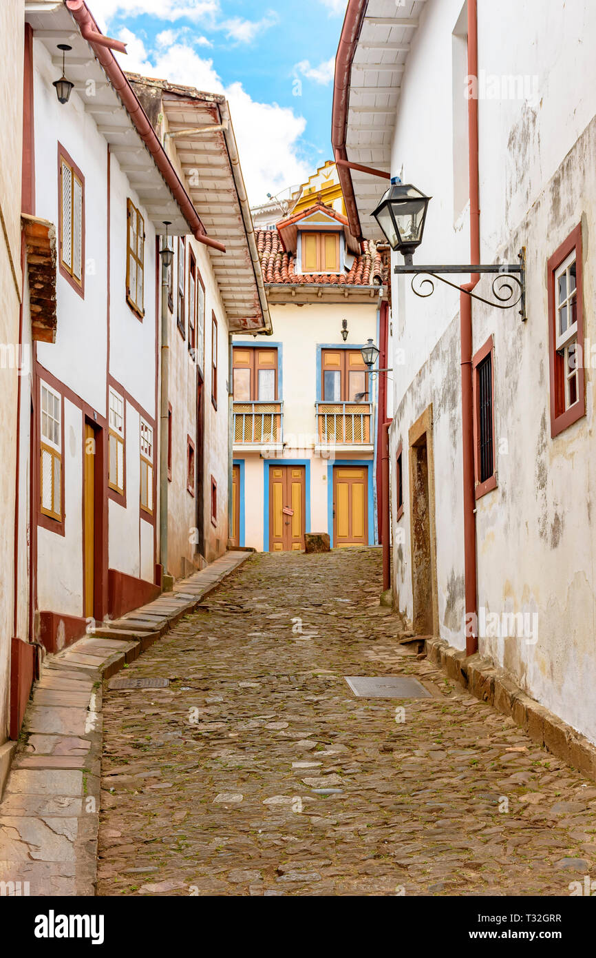 Facade of old houses built in colonial architecture with their balconies, roofs, colorful details and cobblestone street in the historical city of Our - Stock Image