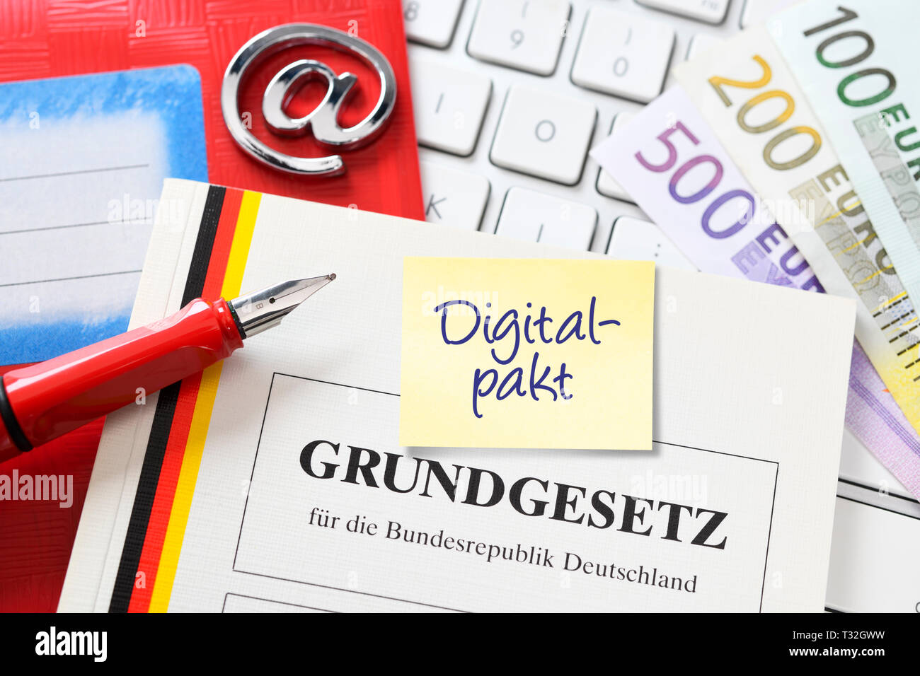 PHOTOMONTAGE, school book, computer keyboard, at-sign, bank notes and basic law, symbolic photo digital pact, FOTOMONTAGE, Schulbuch, Computertastatur - Stock Image