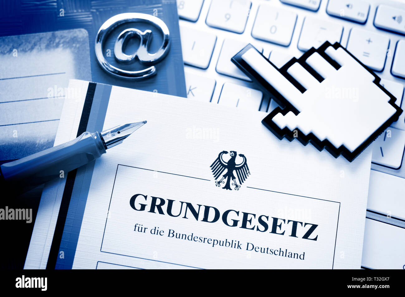 PHOTOMONTAGE, school book, cursor, computer keyboard and basic law, symbolic photo digital pact, FOTOMONTAGE, Schulbuch, Cursor, Computertastatur und  - Stock Image