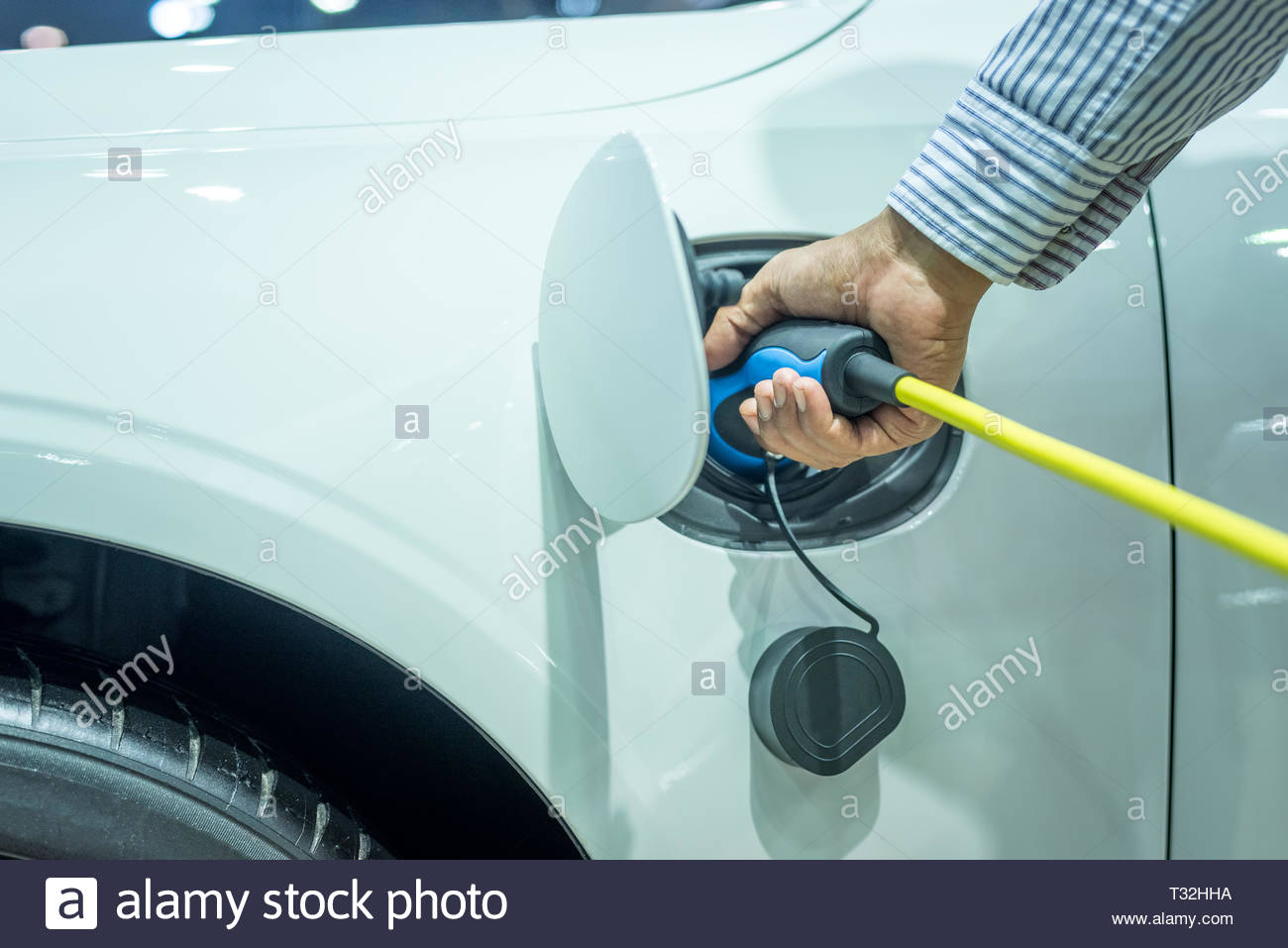 Hand plug the charger access to vehicle electrification. Hybrid car and technology automotive concept - Stock Image