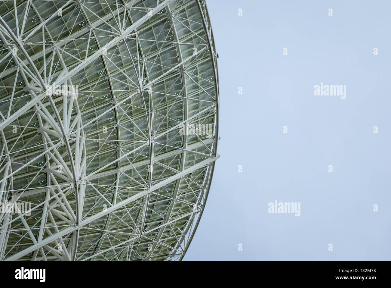 Huge white radio satellite dish isolated against a bright blue sky. - Stock Image