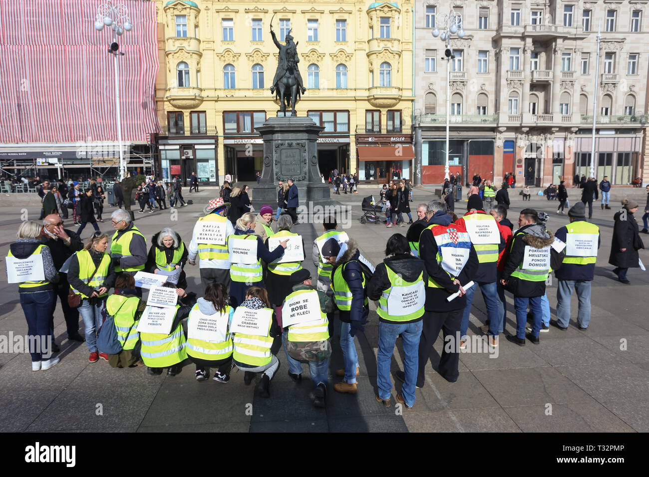 Zagreb, Croatia - February 9, 2019: A group of Yellow vests demonstrators posing with posters with political messages attached to their back at Jelaci - Stock Image