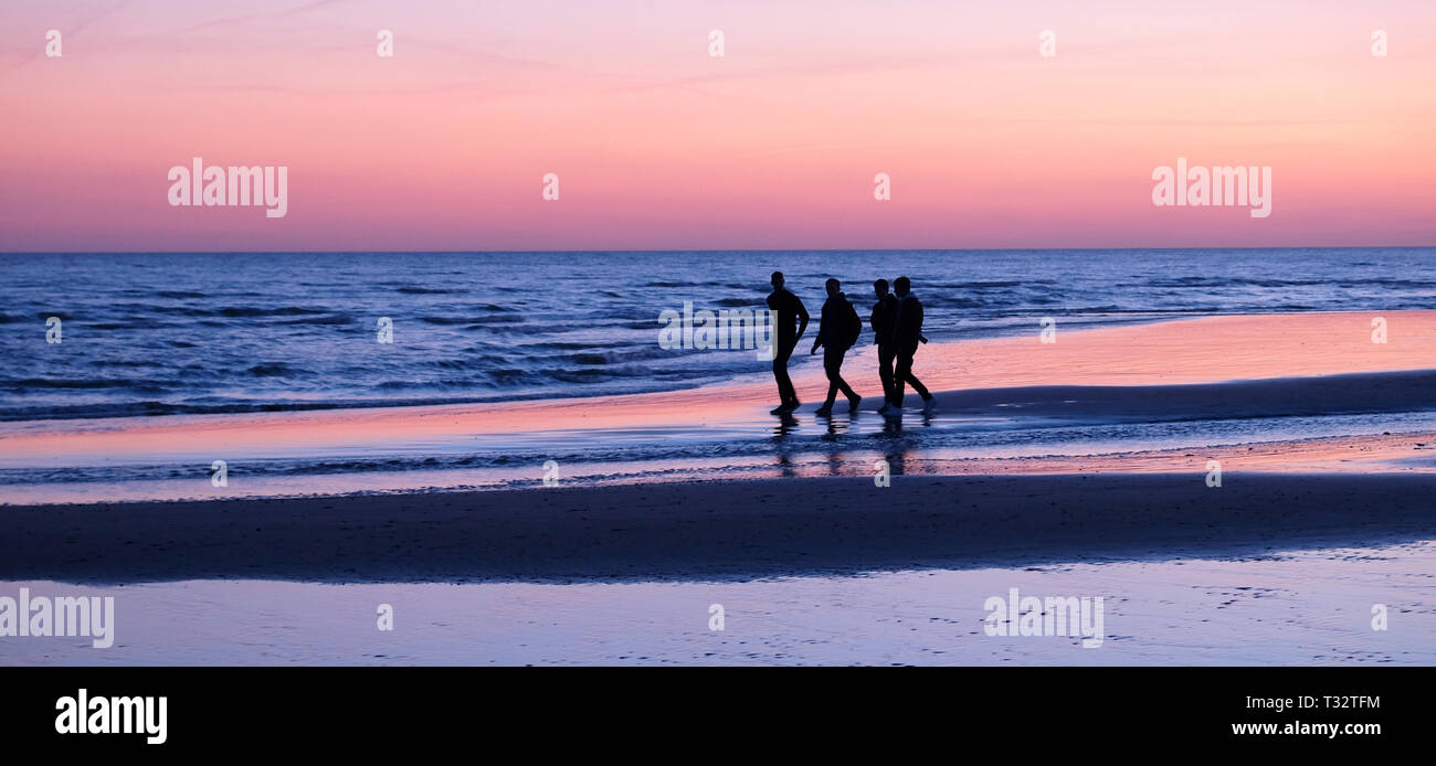 Four unrecognizable young men walking by the sea on a deserted sandy beach, they are close together talking there is a pink glow in the sky reflecting - Stock Image