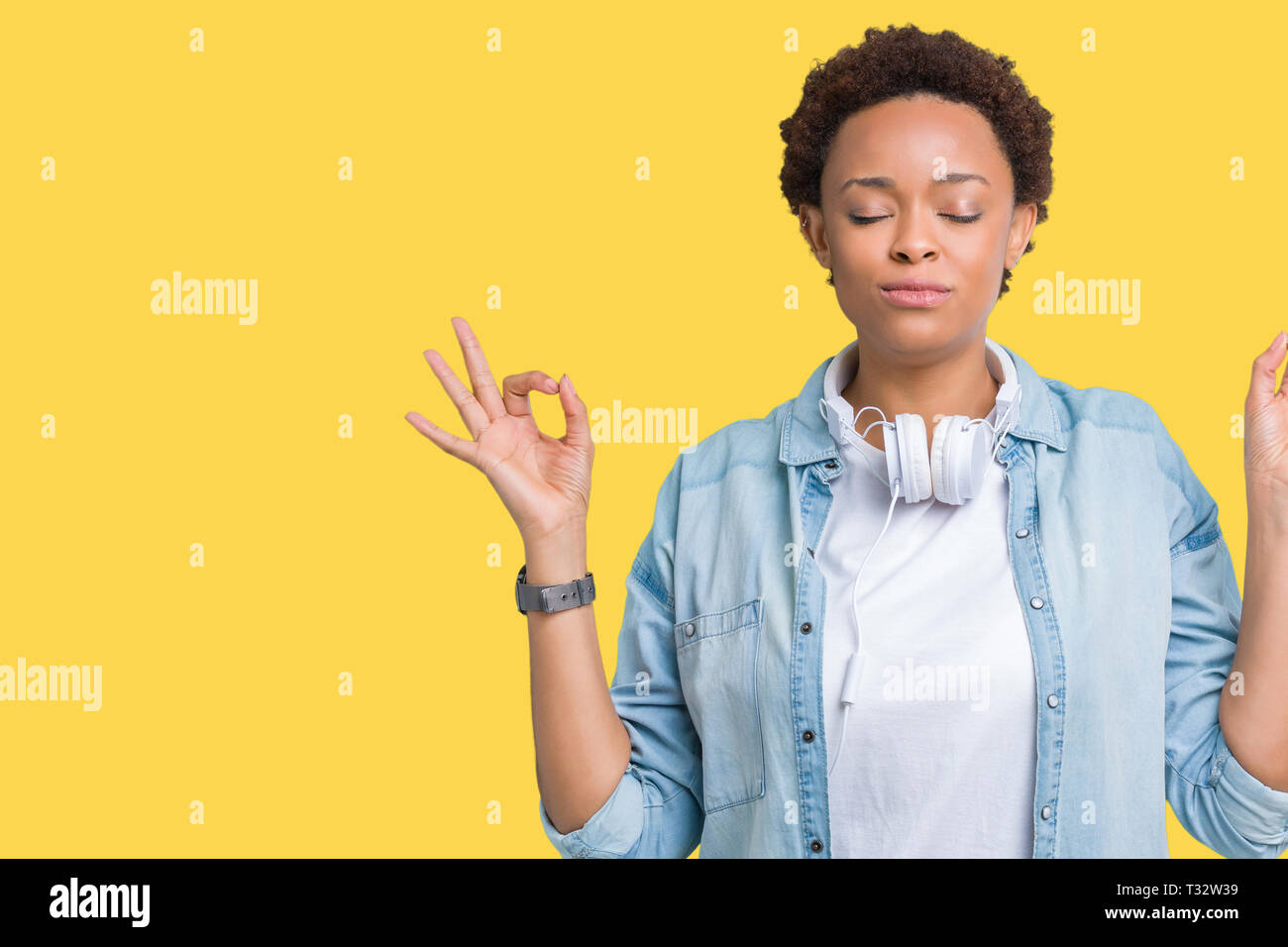 Young african american woman wearing headphones over isolated background relax and smiling with eyes closed doing meditation gesture with fingers. Yog - Stock Image