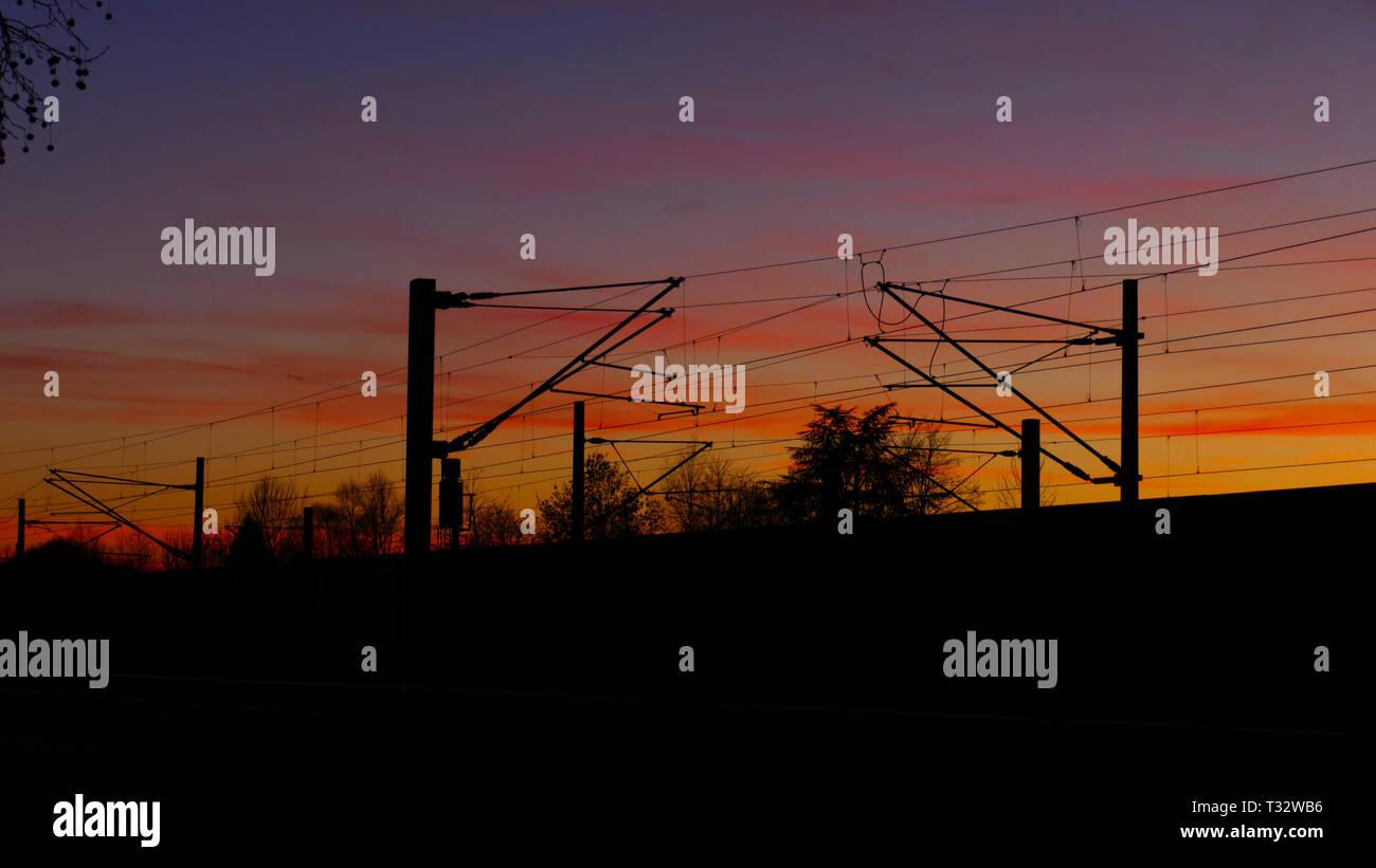 Bahngleise, Oberleitungen, Silhouette mit Bäumen, im Sonnenuntergang - Stock Image