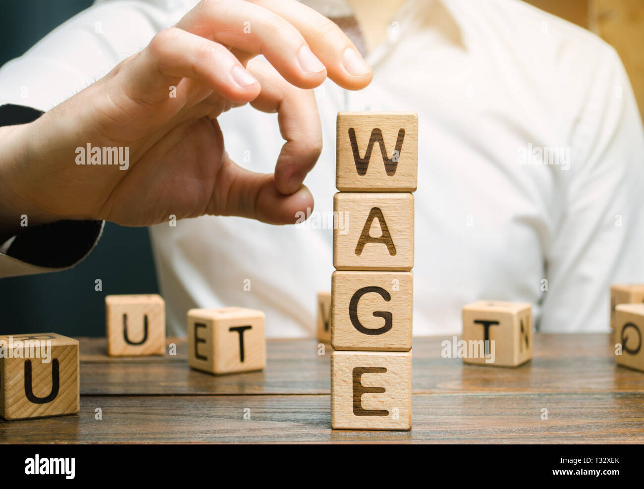 Hand of a businessman removes wooden blocks with the word Wage. Salary reduction concept. Wages cuts. The concept of limited profit. Lack of money and Stock Photo