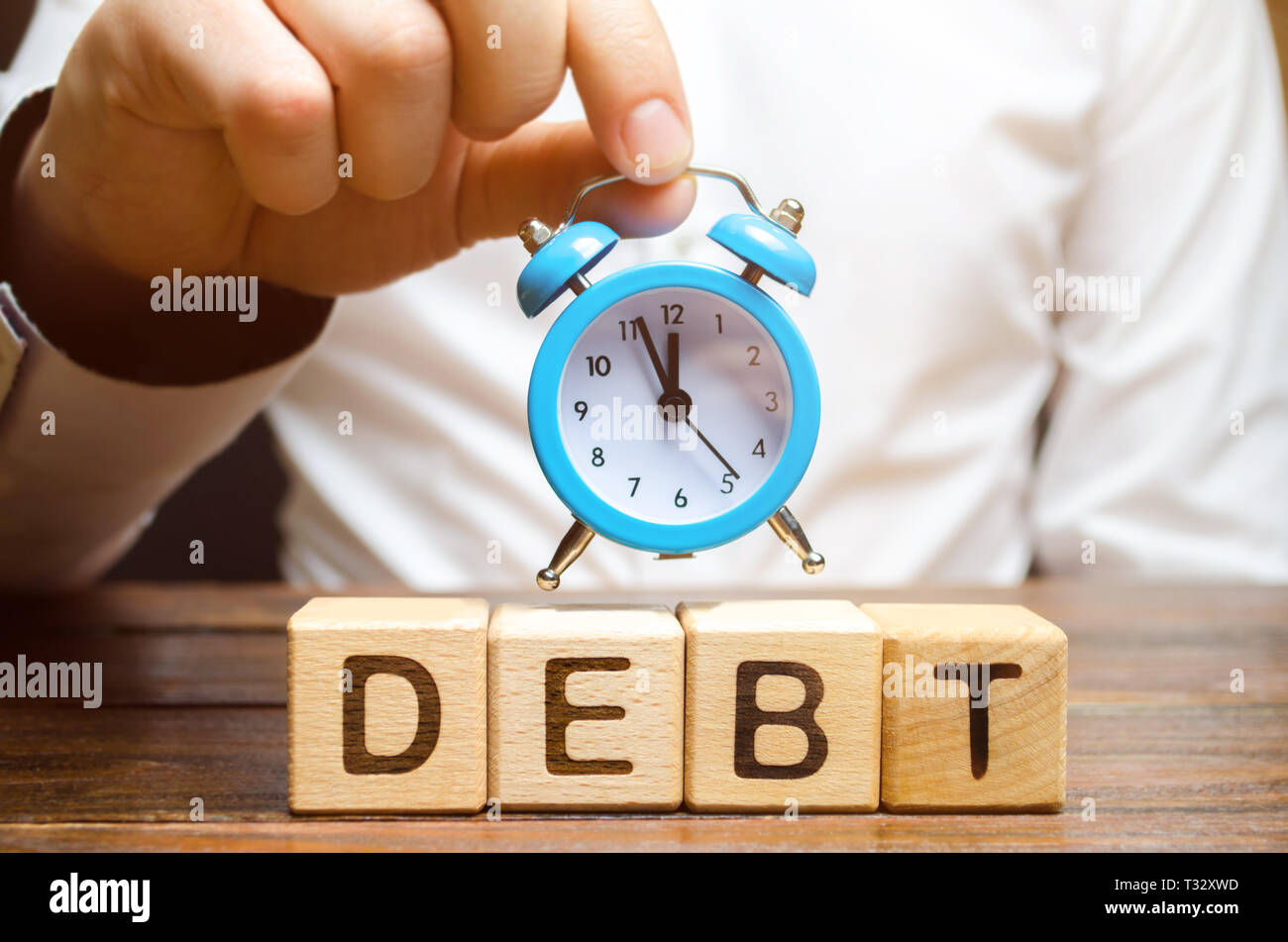 Wooden blocks with the word Debt and the clock in the hands of a businessman. Timely payment of debt. Time to pay off debts. Penalty for late payment  - Stock Image
