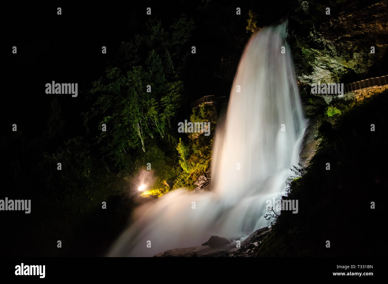 Beautiful waterfall Steinsdalsfossen in Norway shining lit up in the night. - Stock Image