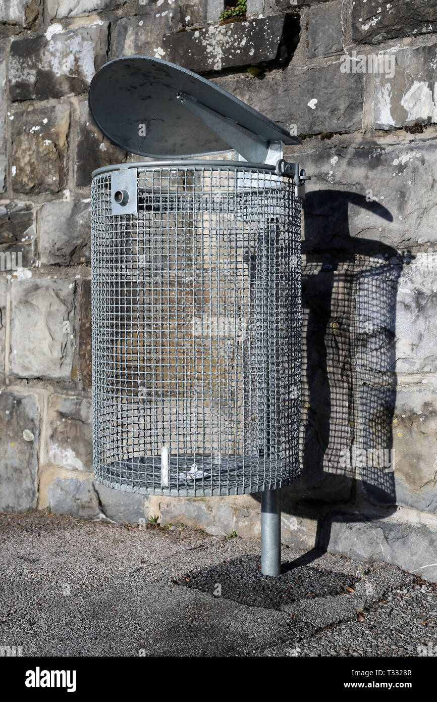 Empty waste bin made of silver colored metal net. Photographed with grey stonewall. Photo was taken outdoors during a sunny day. Stock Photo