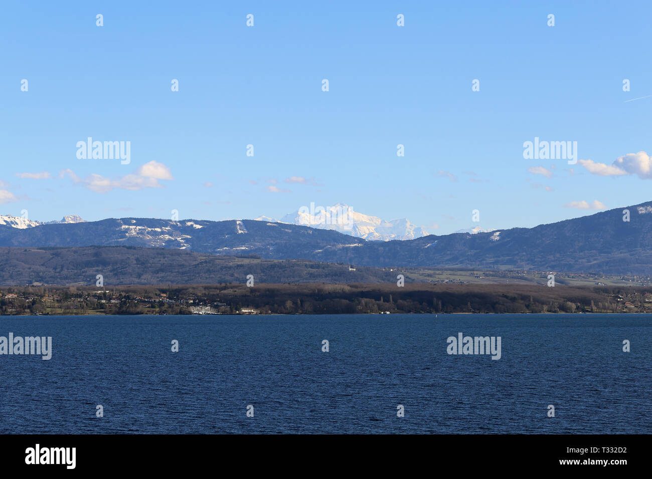 Amazing landscape from Nyon Switzerland. You can see the Alps and some clouds above those mountains. The sky is bright blue and there is clouds. - Stock Image