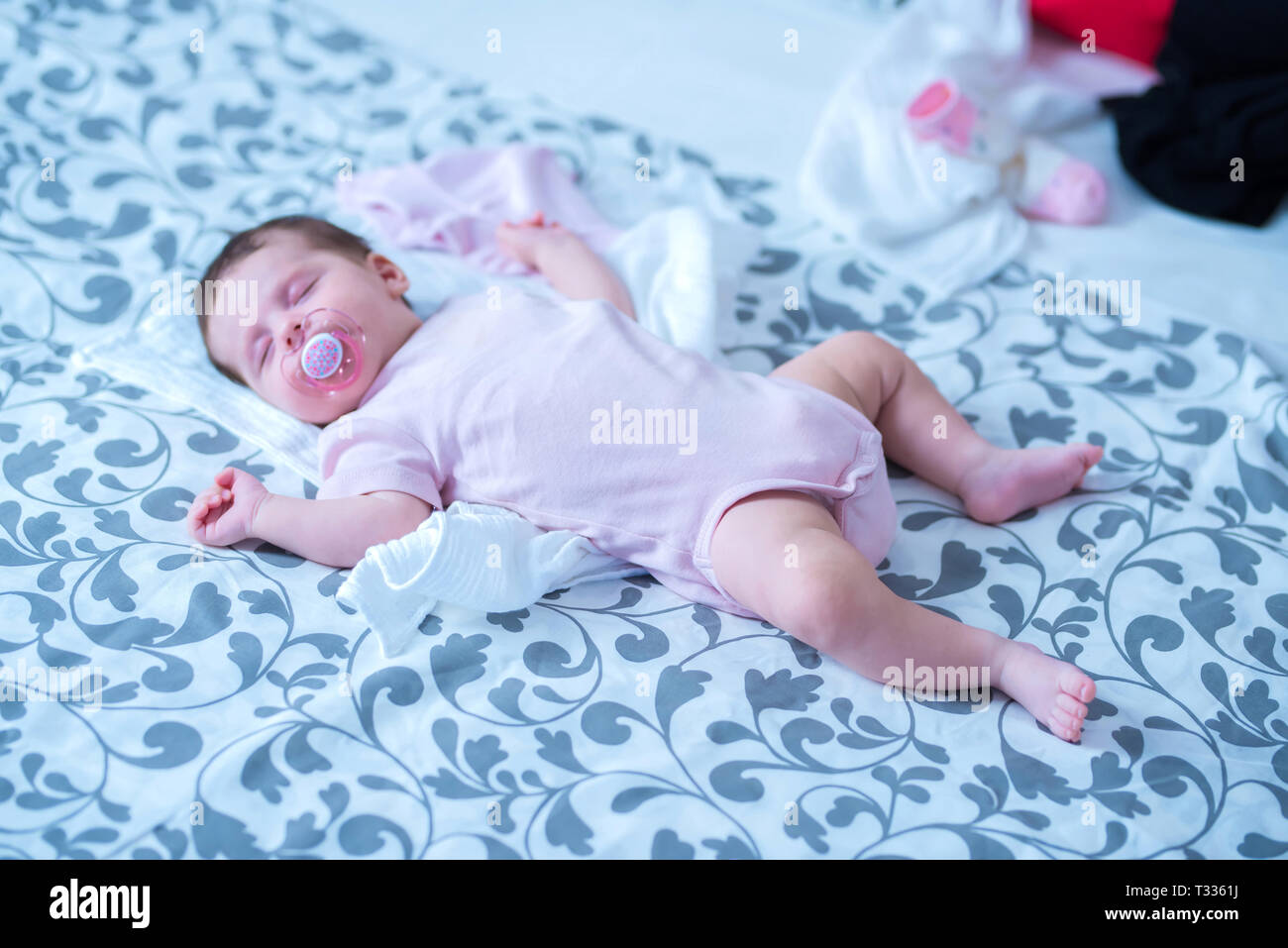 A Cute Baby Girl Lying And Sleeping On A Grey Patterned Blanket With A Dummy In Her Mouth Stock Photo Alamy