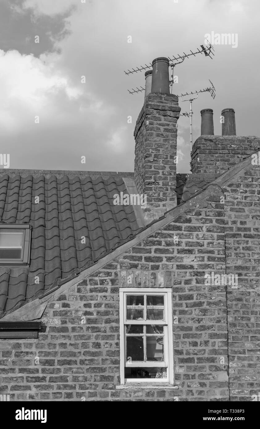 Black and white image of an attic seen from York's ancient city walls. Chimneys and TV arials are above a small sash window. A cloudy sky is above. - Stock Image