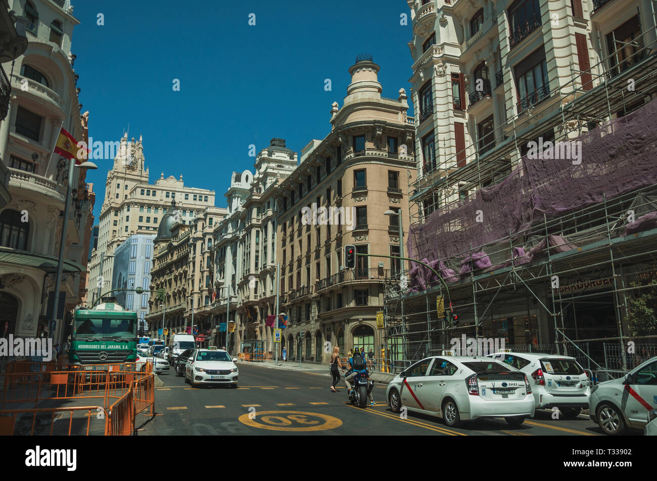 Old buildings with shops on busy street with people and cars, in a sunny day at Madrid. Capital of Spain with vibrant and intense cultural life. - Stock Image