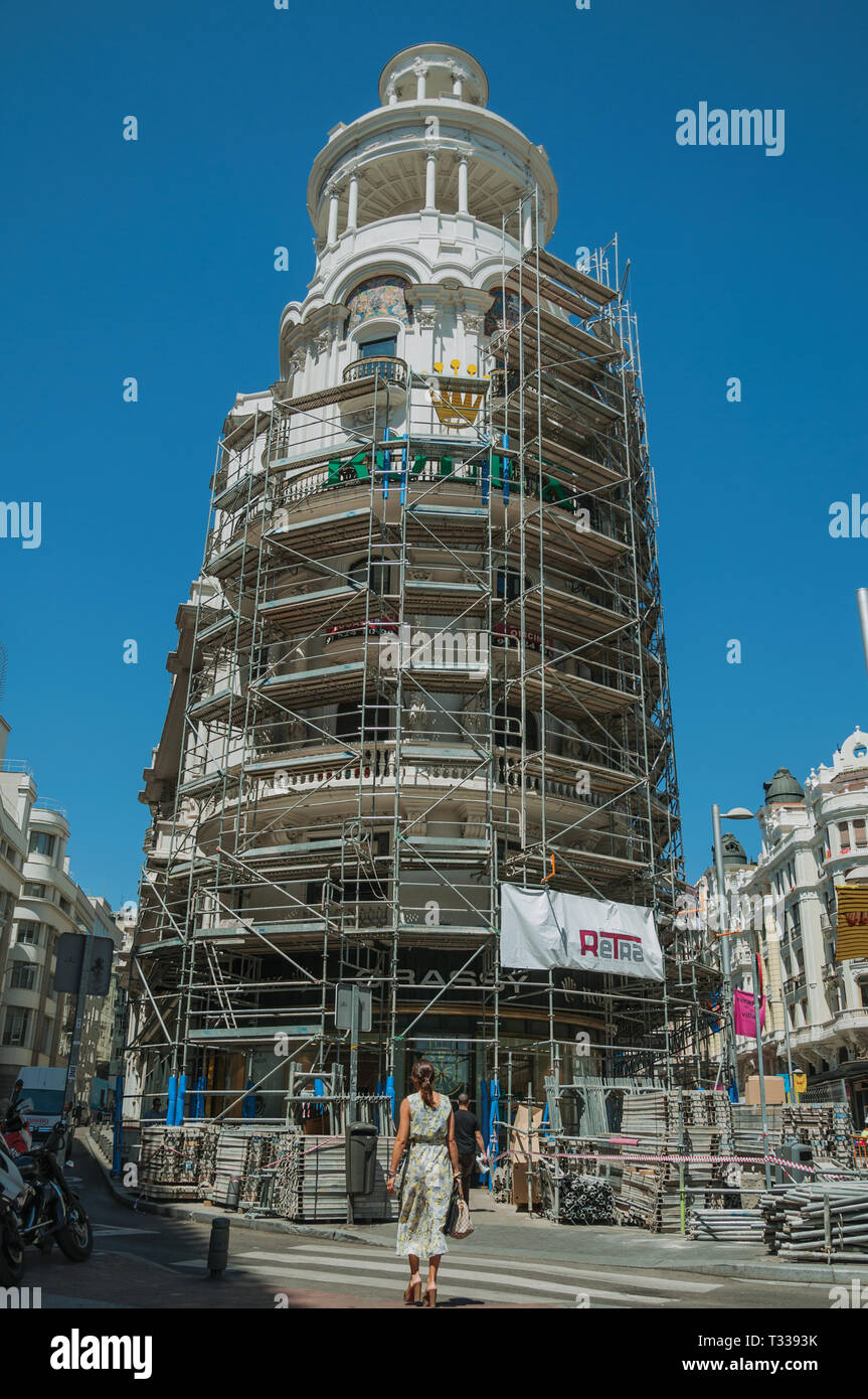 Building being refurbished full of scaffolding on street with woman walking in Madrid. Capital of Spain with vibrant and intense cultural life. - Stock Image