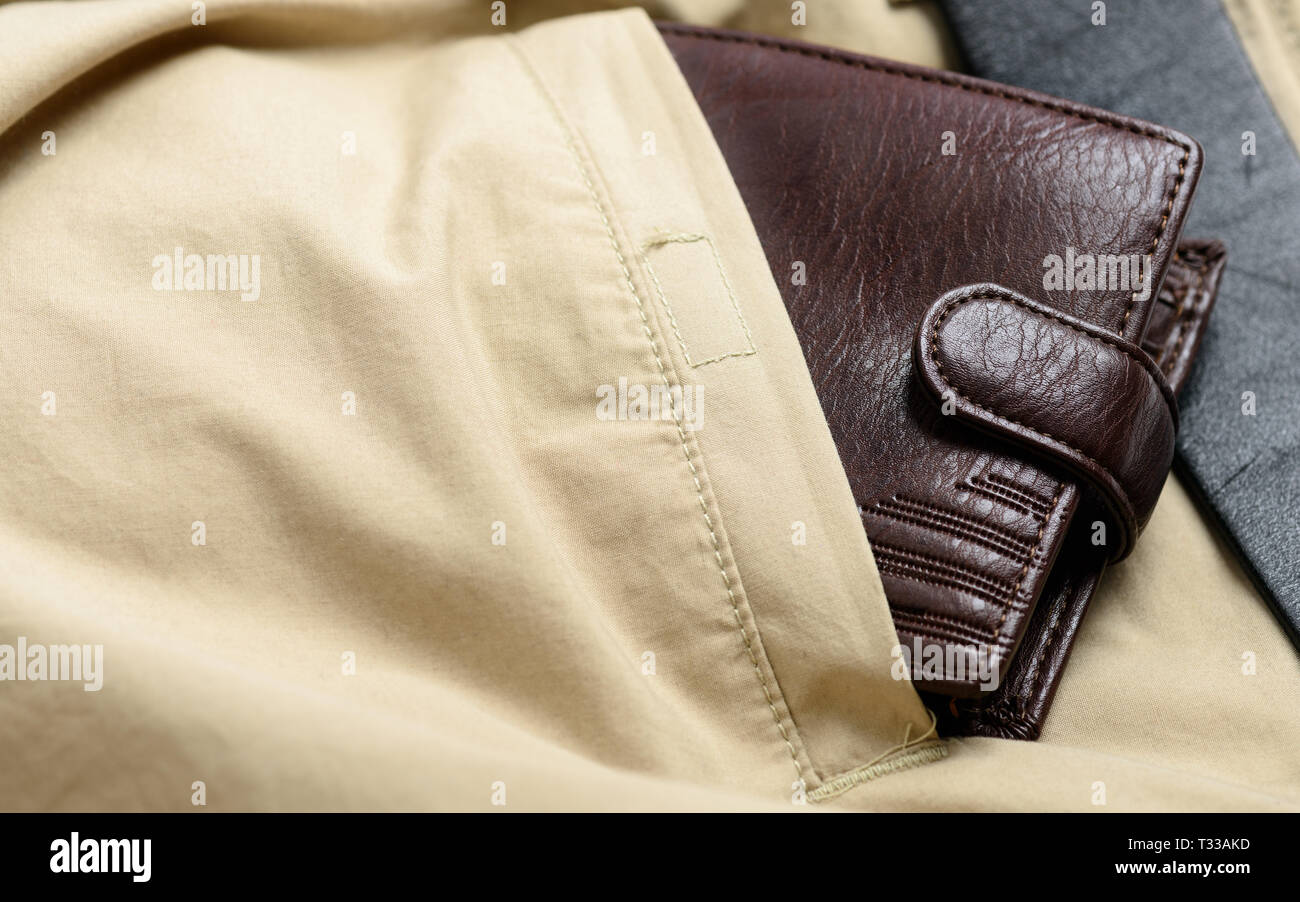 Brown leather wallet in the back pocket of casual pants - Stock Image