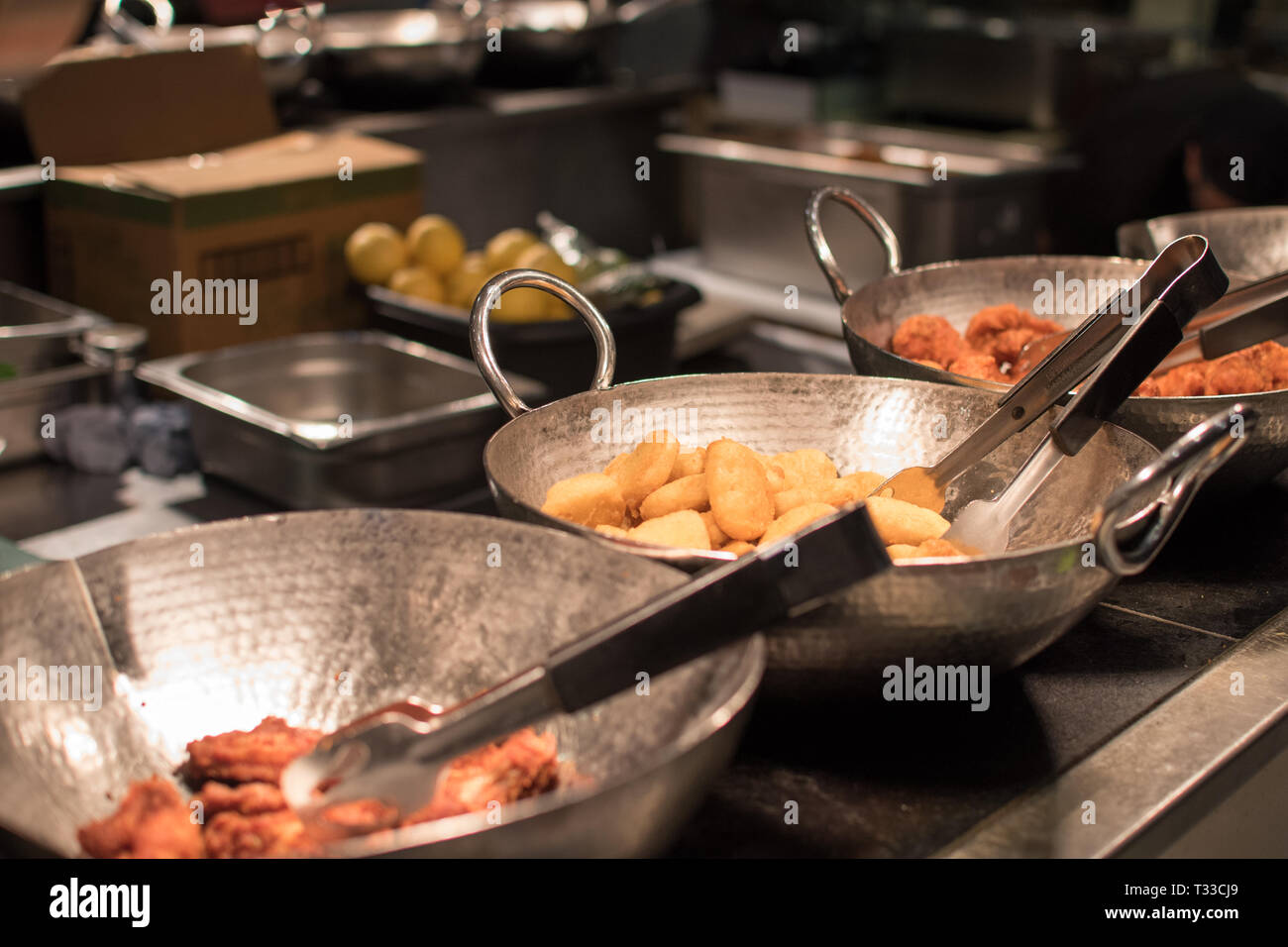 Buffet restaurant with three pans of friend food including chicken wings, chicken nuggets on display under a counter light - Stock Image