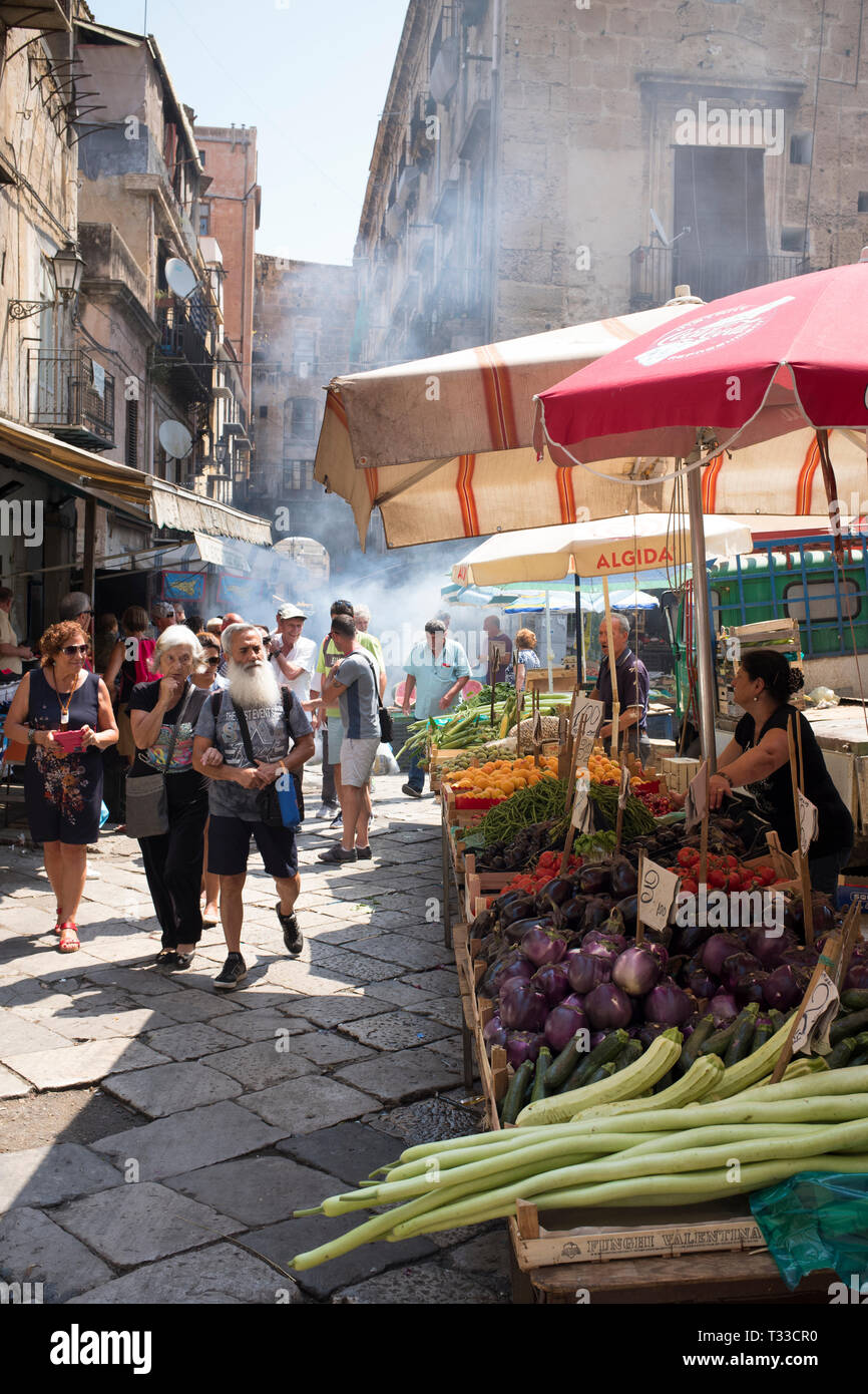 Market stalls, stallholders and customers at the famous Ballero street market for vegetables and other fresh food in Palermo, Sicily, Italy - Stock Image