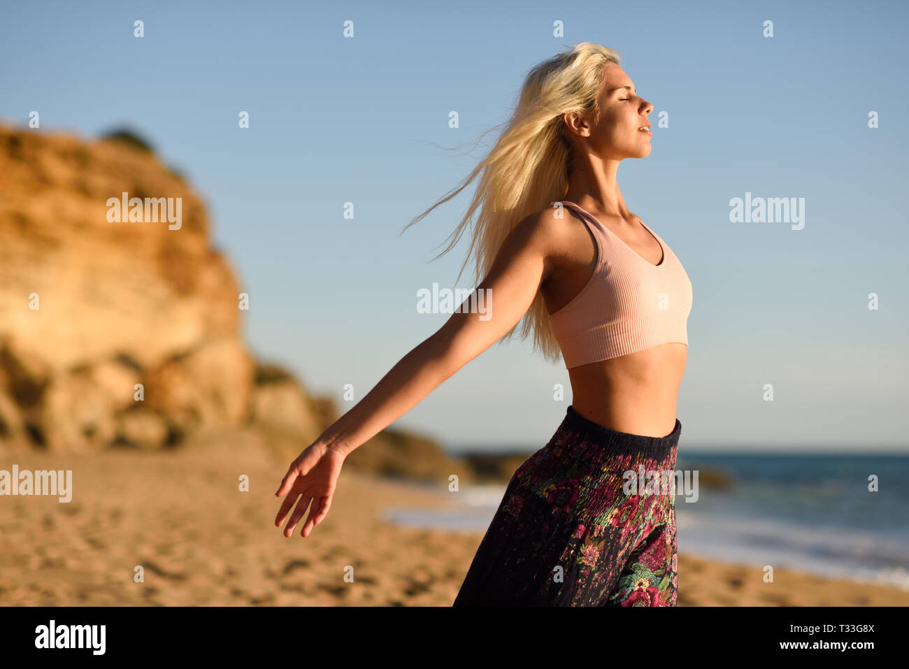 Woman enjoying the sunset on a beautiful beach in Cadiz, Andalusia, Spain. Young female opening arms and breathing the sea air. - Stock Image