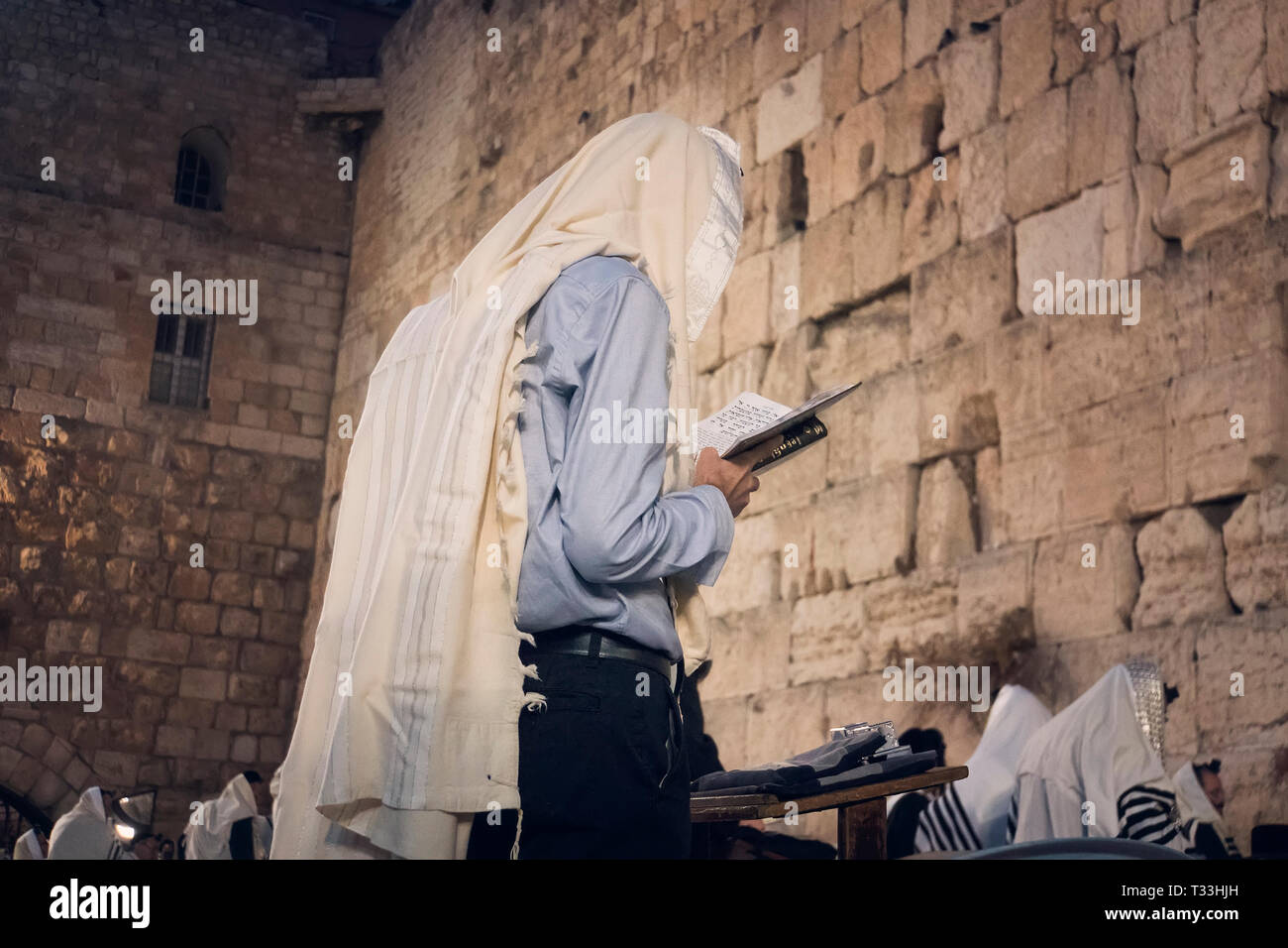 Religion Jew reading prayer book. Torah on the table in front of the wailing wall in the old city of Jerusalem Israel. - Stock Image