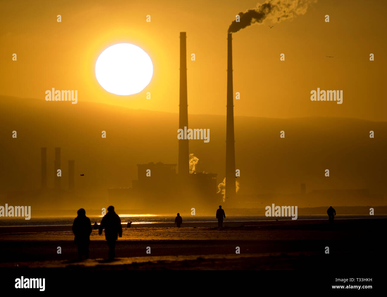 Source of solar energy setting behind user of fossil fuel energy - sun setting behind Poolbeg Generating station, Ringsend Dublin, The Walkers are on  - Stock Image