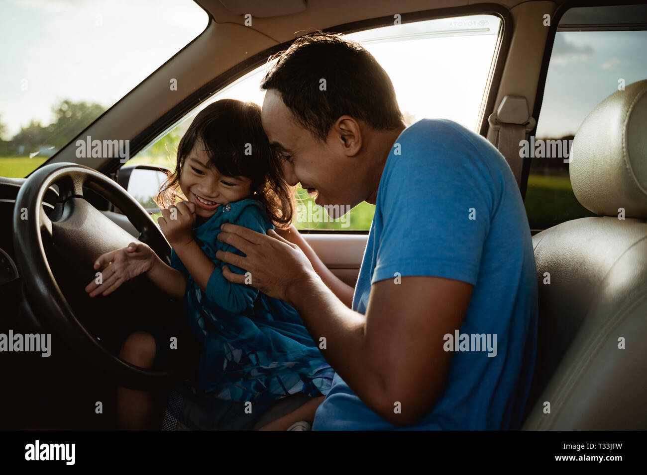 daddy tickling her little girl in the car Stock Photo