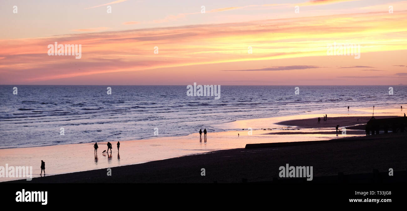 Brighton beach, England, UK, at low tide with unrecognizable people walking along the shoreline at sunset, the people are silhouetted by the orange gl - Stock Image