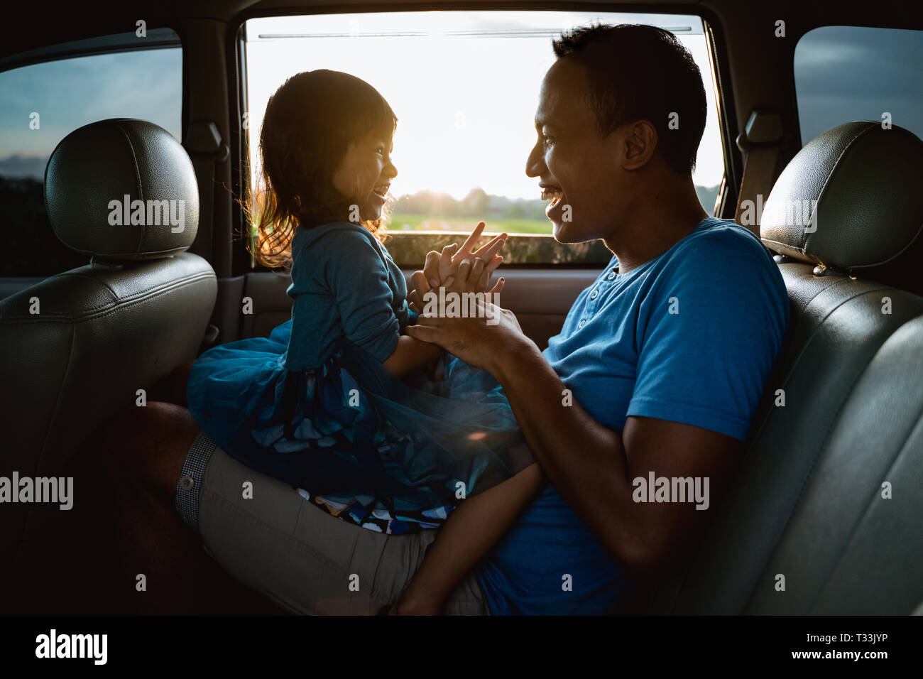 asian daughter with father in the car playing Stock Photo