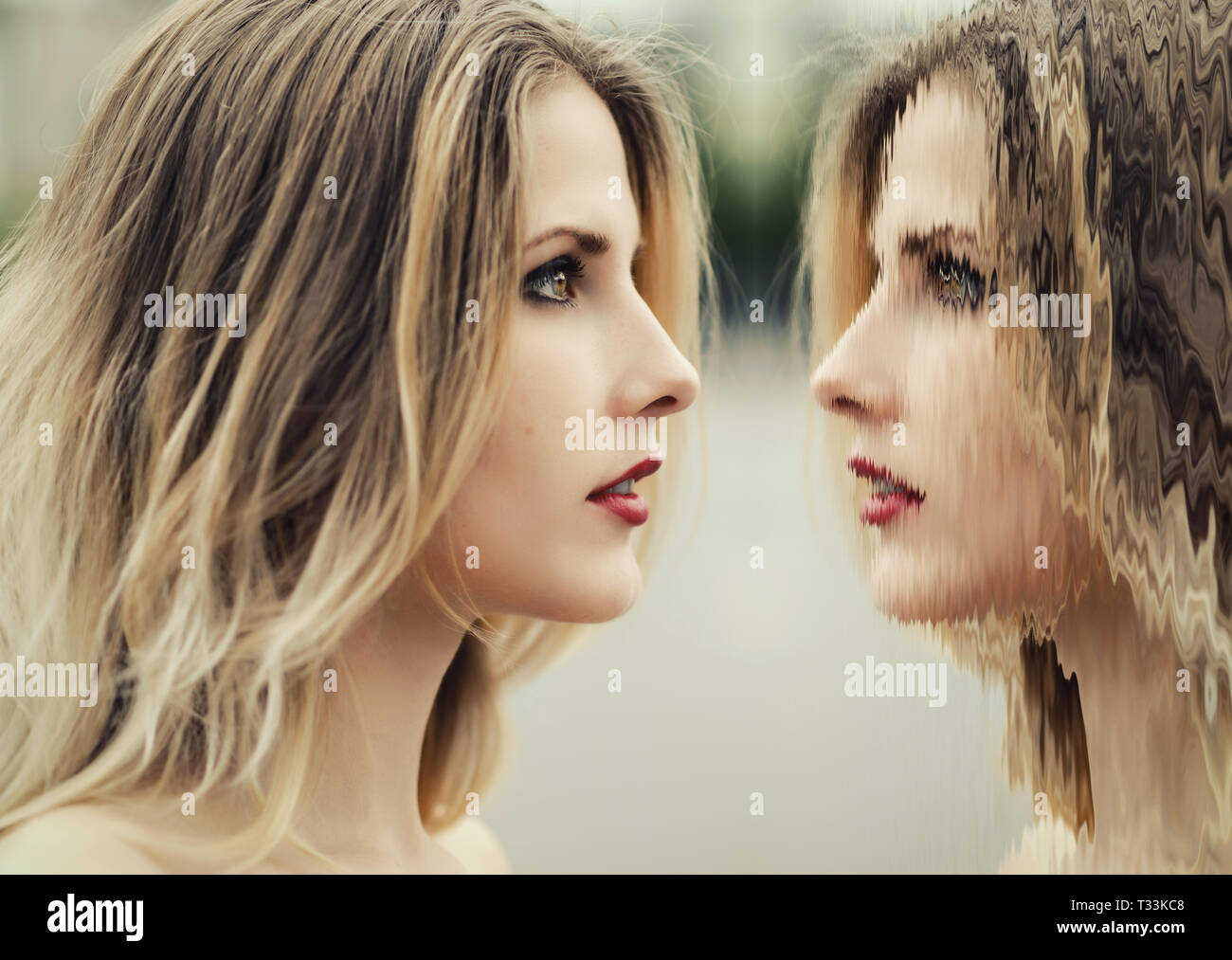 Young woman looks at her reflection in mystical mirror. - Stock Image