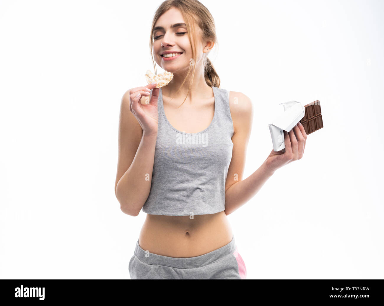 Diet. Dieting concept. Healthy Food. Beautiful Young Woman choosing between Healthy and Unhealthy Food.Fruits or Sweets. Isolated on a White Backgroun - Stock Photo